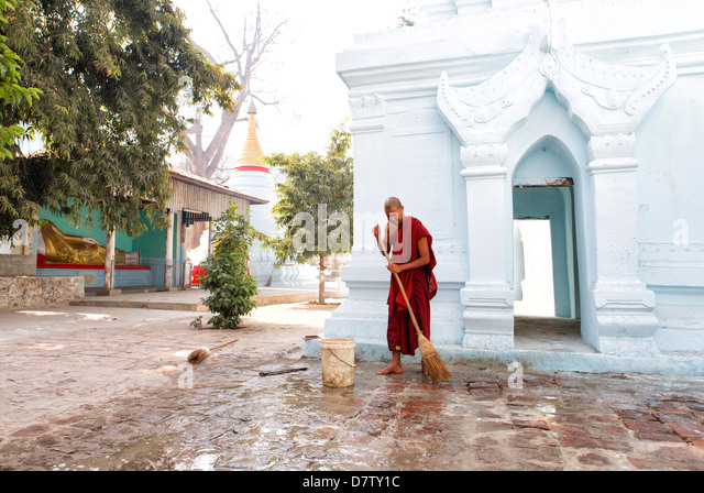 Buddhist monk cleaning paving outside a small temple near the famous U Bein teak bridge, Amarapura, near Mandalay, - Stock-Bilder