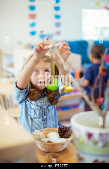 Student playing with model in classroom - Stock Image