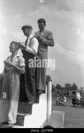 1950s, historical, three male timekeepers on an elevated wooden timekeeping stand make notes as they check the finishers - Stock Image
