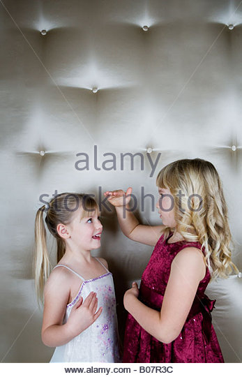 Two friends in party dresses measuring each other - Stock Image