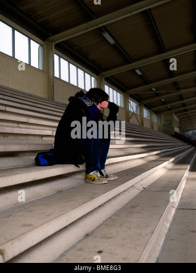 Boy sitting on staircase in depression - Stock Image