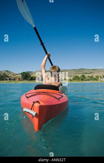 Boy paddling in canoe on lake, Utah, United States - Stock Image