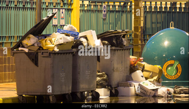 Overflowing rubbish containers in street in Spain - Stock Image