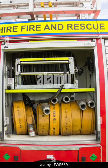 Compartment of rolled fire hoses on a fire engine. The vehicle is a DAF LF series truck with coachwork by Browns - Stock Image