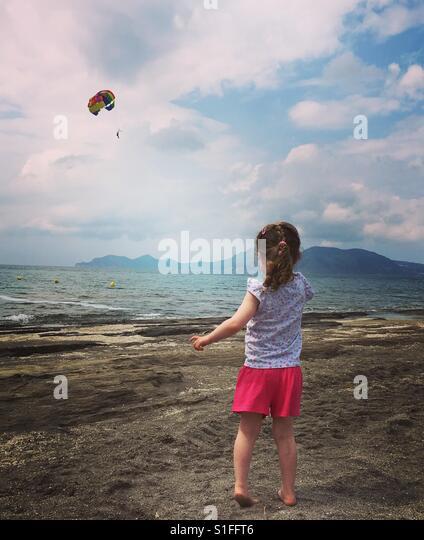 Little girl watching father parascending - Stock-Bilder