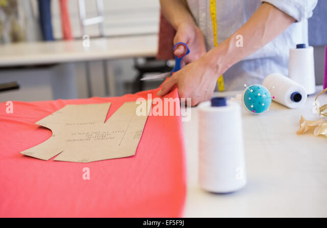 Student cutting fabric with pair of scissors - Stock-Bilder