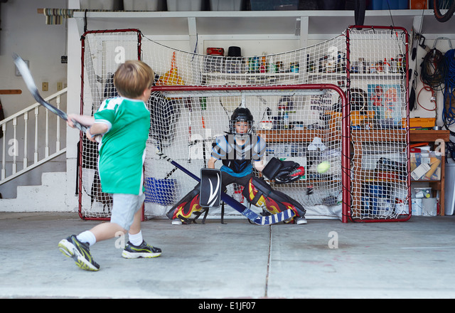 Boys playing hockey in garage - Stock Image