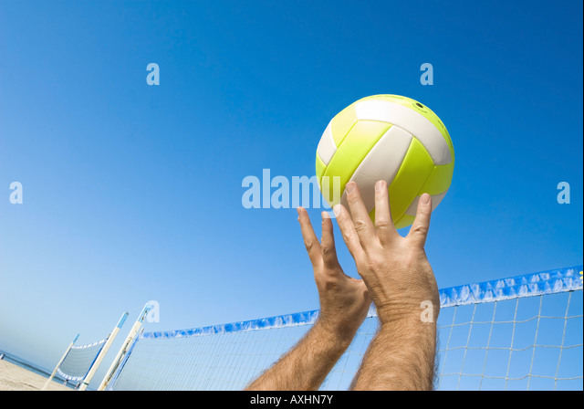 A volleyball player lobs a ball during a game at the beach - Stock Image