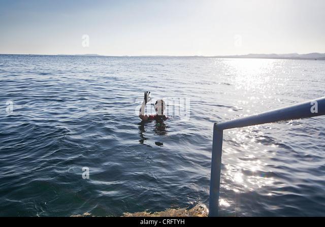 Snorkeler making OK sign in water - Stock-Bilder