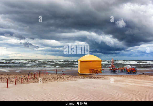 Yellow tent cafe with tables and chairs under a sky with beautiful clouds on the shore of a sandy beach in a storm - Stock Image