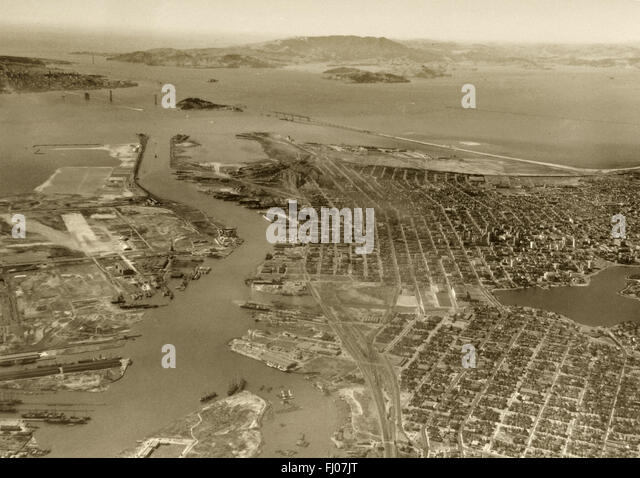 historical aerial photograph of Oakland, Alameda, Port of Oakland with Bay Bridge and Golden Gate Bridge under construction, - Stock Image