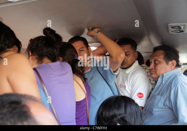 Nicaragua Managua bus microbus public transportation Hispanic man woman crowded standing room - Stock Image