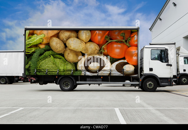 Truck with vegetables parked outside distribution warehouse - Stock Image