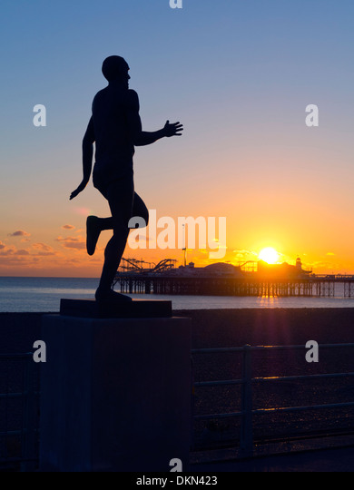 Statue of Olympic athlete Steve Ovett framed by Brighton Pier and the setting sun - Stock Image