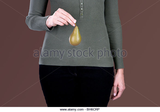 A woman holding a pear in front of her hips - Stock Image