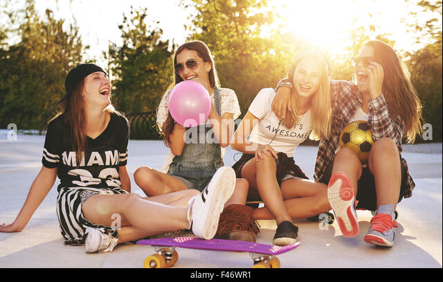 Friends having fun in a park with skateboards and sunglasses - Stock Image