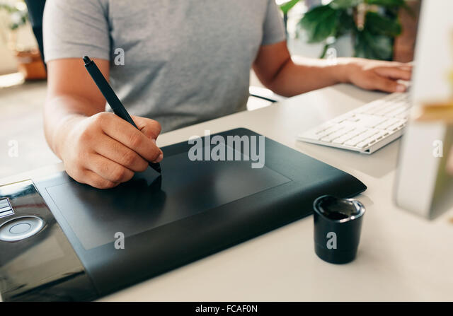 Graphic designer using digital tablet and desktop computer in the office. Close-up of designer's hand working - Stock-Bilder