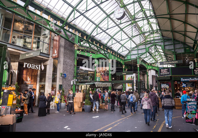 LONDON - OCTOBER 31, 2016: Visitors browse the stalls at Borough Market, home to one of the largest and oldest markets - Stock Image