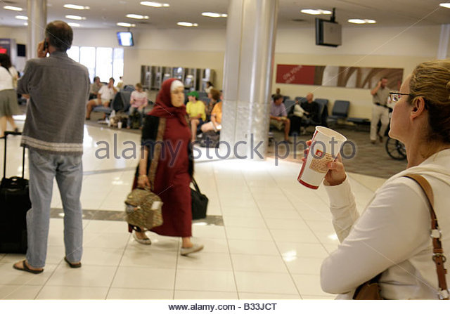 Atlanta Georgia Hartsfield-Jackson Atlanta Airport ATL concourse passenger woman women Muslim hijab coffee cup gate - Stock Image