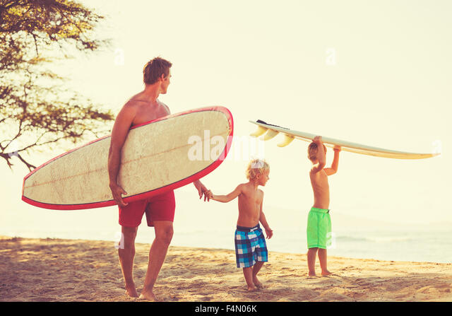 Father and sons going surfing together. Summer fun outdoor lifestyle - Stock Image