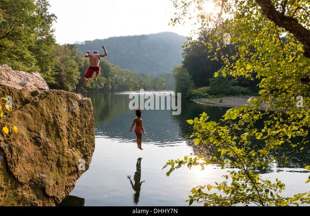 Young couple jumping from rock ledge, Hamburg, Pennsylvania, USA - Stock-Bilder