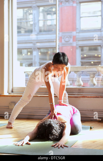 Yoga teacher assisting woman in class - Stock Image
