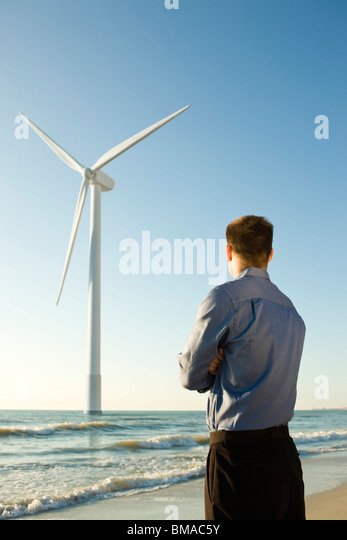 Businessman on beach looking at offshore wind turbine - Stock Image