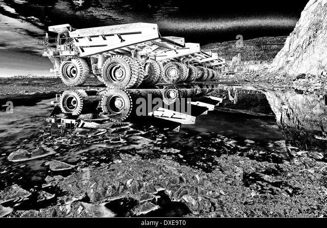 Abstract art picture of catapillar trucks in a quarrie.black and white. - Stock Image