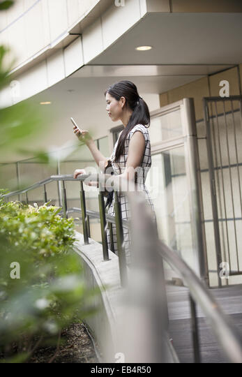 A woman on a walkway in Namba Park office and shopping complex. - Stock Image