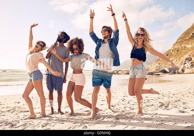 Portrait of excited young friends standing on the beach. Multiracial group of friends enjoying a day at beach. - Stock Image