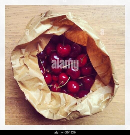A paper bag full of ripe red cherries fresh from the market - Stock Image