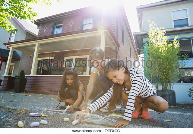 Mother and daughters drawing with sidewalk chalk - Stock-Bilder