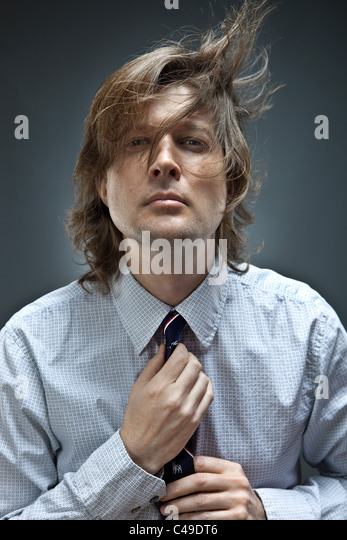 Studio shot of man in button-down oxford shirt adjusts his tie while his brown hair blows around. - Stock Image