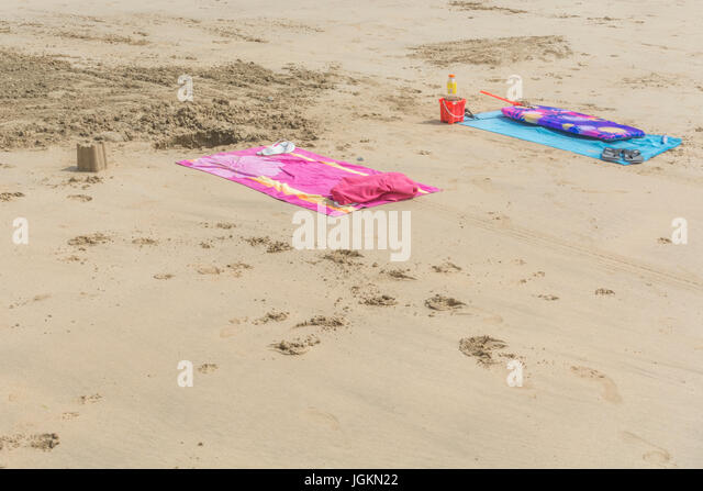 Two beach towels on the beach at Newquay, Cornwall. - Stock Image