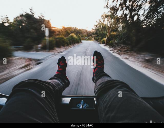 Low Section Of Person Relaxing In Moving Car On Road - Stock Image