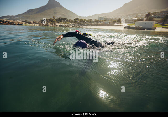 Athletes in the swim event of a triathlon competition. Triathletes swimming in open water. - Stock Image