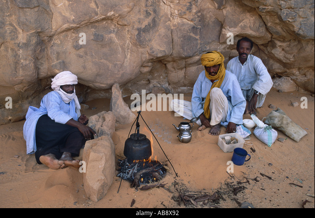 three Touareg sitting beside a campfire, Algeria, Suedalgerien - Stock Image