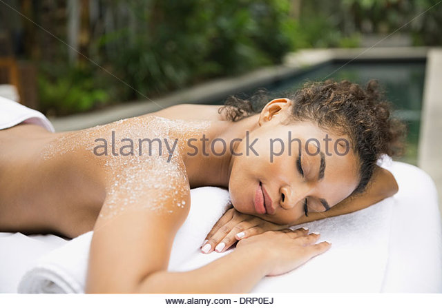 Relaxed woman at day spa receiving body scrub - Stock Image