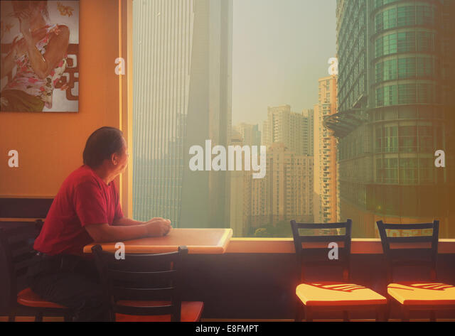 China, Shanghai, Man sitting at table - Stock Image
