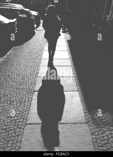 Rear View Of Woman Walking On Sidewalk During Sunny Day - Stock Image