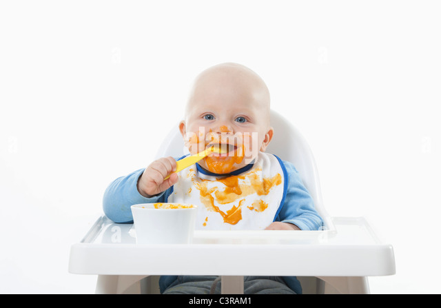Baby boy (6- 11 Months) eating baby food with baby spoon - Stock Image