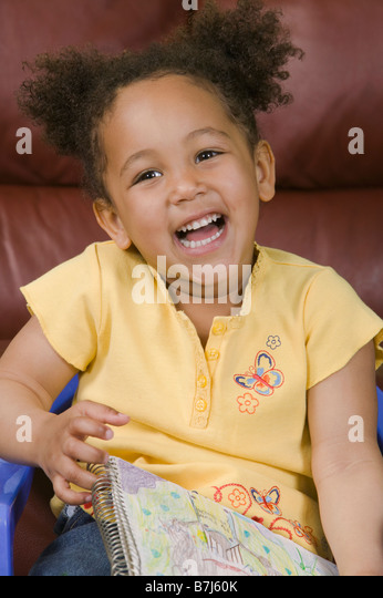 Mulatto girl and her artwork (3 years old). - Stock Image