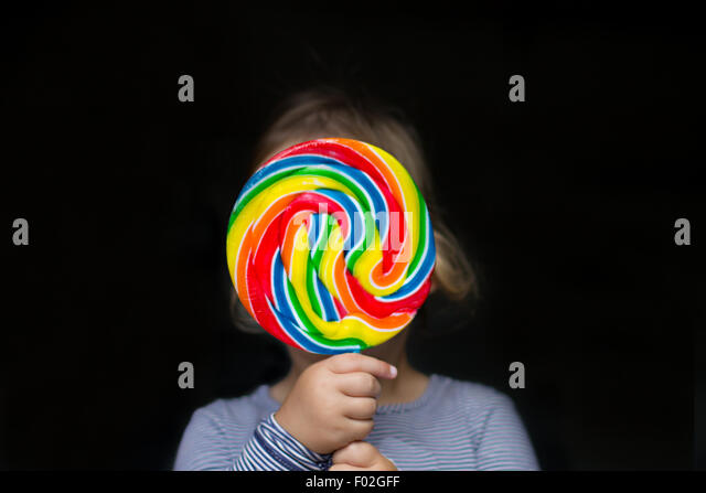 Portrait of a girl holding a multi-colored lollipop - Stock Image
