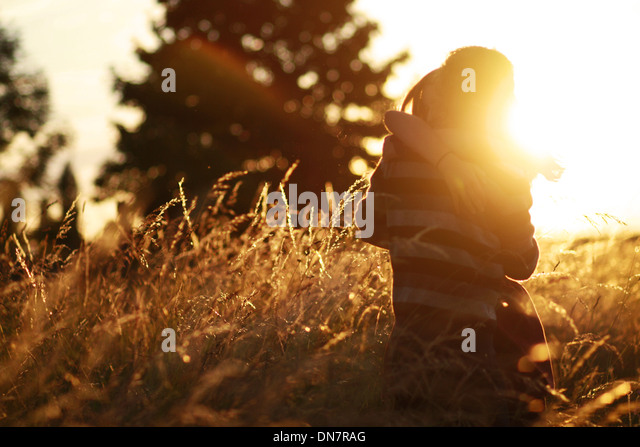 Young couple in love in the cornfield, kissing in backlight - Stock Image