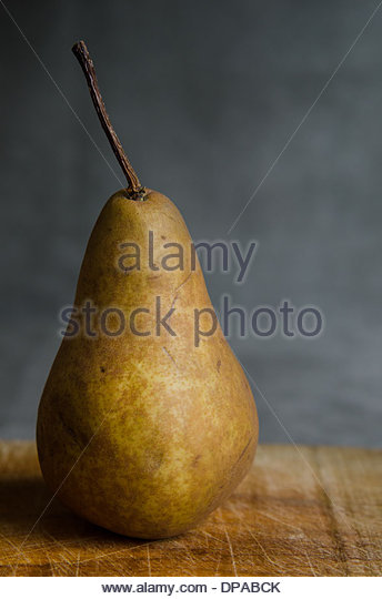One whole bosc pear on wooden board in window light and dark background. - Stock Image
