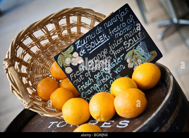 Basket of local oranges outside a street cafe in Port-de-Soller, Mallorca - Stock-Bilder