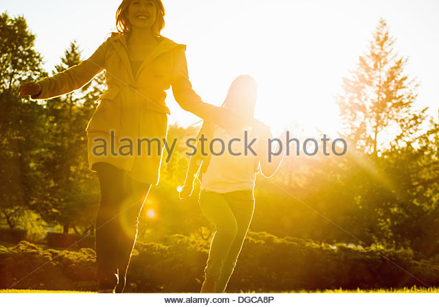 Two young women running in park - Stock Image