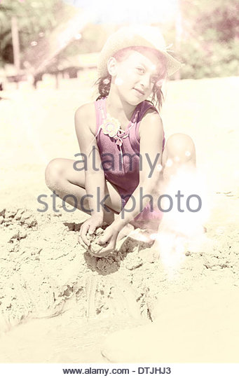 Artistically aged and faded vintage photo of a young girl in a hat playing in the sand on a beach in a grunge summer - Stock-Bilder