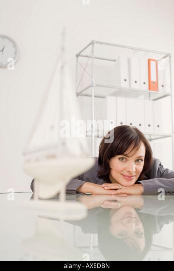 Businesswoman looking at ship model - Stock-Bilder