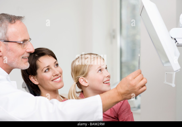 Dentists and patients looking at monitor - Stock Image